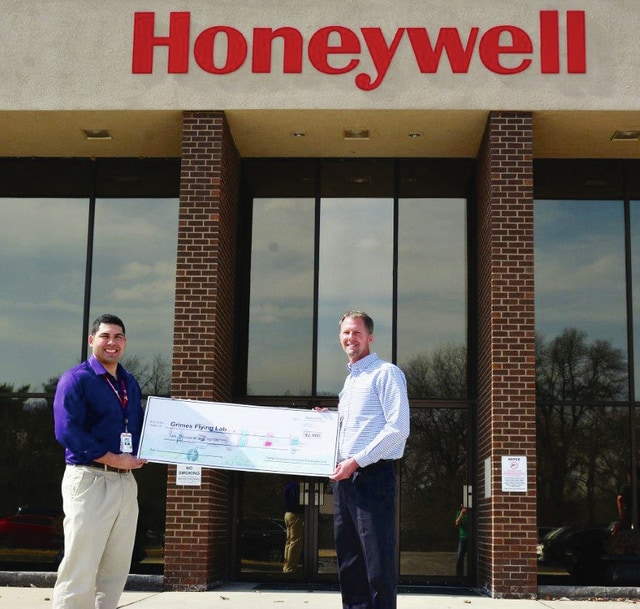 Honeywell Aerospace Senior Director/Plant General Manager Tom Duggan, left, presents a $2,000 check to Randy Henson, right, vice president of the Grimes Flying Lab Foundation Board.
