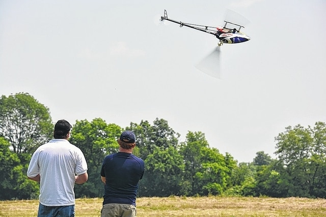 Two eventgoers view activities at last year's Mad River Flying Association Helicopter Fly-In at MRFA's flying field at 1217 Childrens Home Road in Urbana. The MRFA Swap Meet will be held Saturday at the Champaign Aviation Museum at 1652 N. Main St., Urbana.