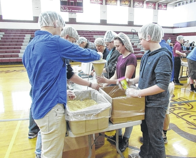 Urbana FFA members and volunteers from Rittal Corporation in Urbana package soy-fortified macaroni and cheese meals for Champaign County food pantries in partnership with Meals of Hope.