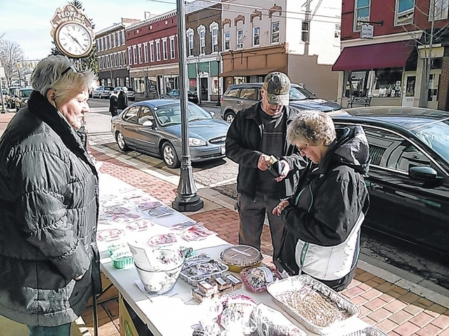 Bicentennial Committee member Bobbi Gratz sells to supporters Lloyd and Sue Oliver during the bake sale.