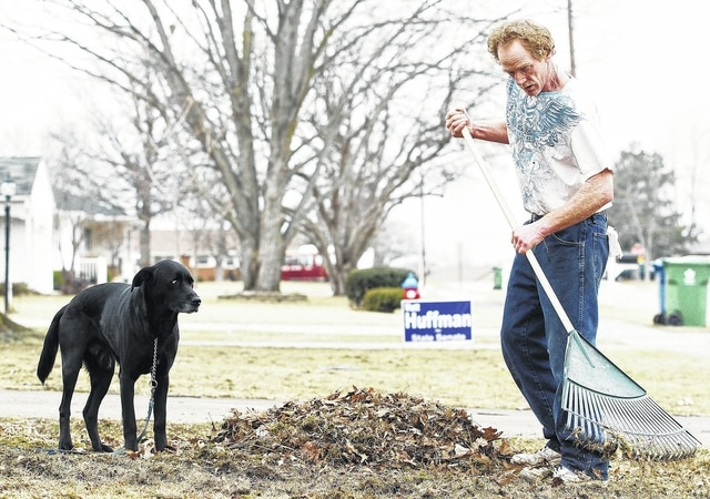 Darin Reineke, of Sidney, rakes up dead leaves on his front lawn on Parkwood Street under the protective gaze of his dog Tuesday, March 1. Reineke said he was getting rid of the old leaves so the grass can get growing.