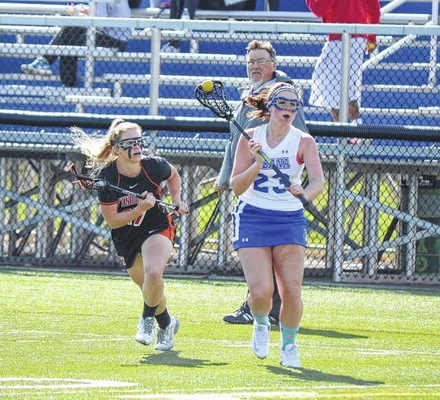 Urbana University's Sami Secrest looks for a teammate to pass to Wednesday against the University of Findlay in women's lacrosse.