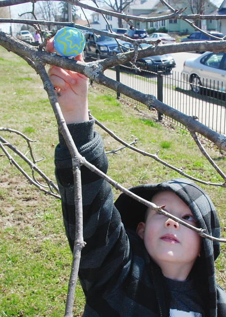 Michael Barnett reaches for an Easter egg hidden in a tree that the horde of hunting children had missed just seconds earlier.