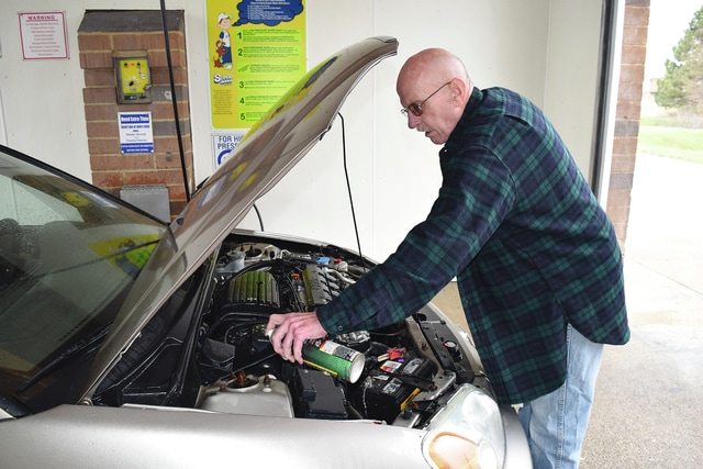 Ed Brown of Urbana finishes prepping his car for warmer weather on Monday by applying WD-40 under the hood. Stray snowflakes are in the long-term forecast, but the first part of March has been an early taste of spring and a chance to get ready for summer.