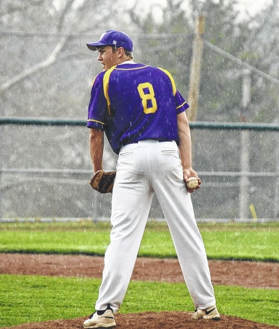 Mechanicsburg's Caleb Newsome gets set for a pitch in the heavy rain against Triad on Thursday. The game was delayed due to the weather.