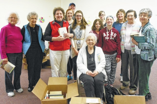 Participants take a pause from sorting and boxing 1360 books for the C.A.R. book drive. Books were delivered the following day to charities in Columbus. From left are Judith Henson, Regent of Urbana Chapter DAR, Janet Anderson, Urbana Chapter Member, Kim Snyder, Senior President Cuttahotha Society C.A.R. and Urbana Chapter Member Camille Brinnon, Secretary Cuttahotha Society C.A.R., Evan Brinnon, President Cuttahotha Society C.A.R., Megan Snyder, Cuttahotha Society Member, Sarah Preston, Cuttahotha Society Member, Becky Preston, Cuttahotha Society Member, Ericka Crook, guest Karen Preston, Urbana Chapter Member, Betty Driever Urbana Chapter Registrar, Margaret Denzer, Urbana Chapter Librarian. Seated is Janet Ebert, former C.A.R. Society Senior President, Urbana Chapter Historian.