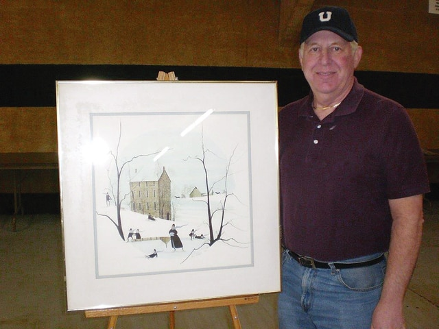 """Local auctioneer Steve Mabry is pictured displaying a P. Buckley Moss signed artwork which will be auctioned during the Champaign County Preservation Alliance's annual Décor and More auction to be held Saturday, April 30, beginning at 1:01 p.m. Donations are being accepted April 25-28 from 11 a.m. to 3 p.m. at Mabry's Auction Gallery, 1301 N. Main St. Marty Hess and Vince Gonzalez, emcees for the auction, guarantee an afternoon of fun and a great variety of """"treasures"""" to sell. Contact Barbara Perry with any questions, 653-4776. Proceeds from the auction will fund the Commercial and Retail Façade Grant program sponsored by the CCPA."""