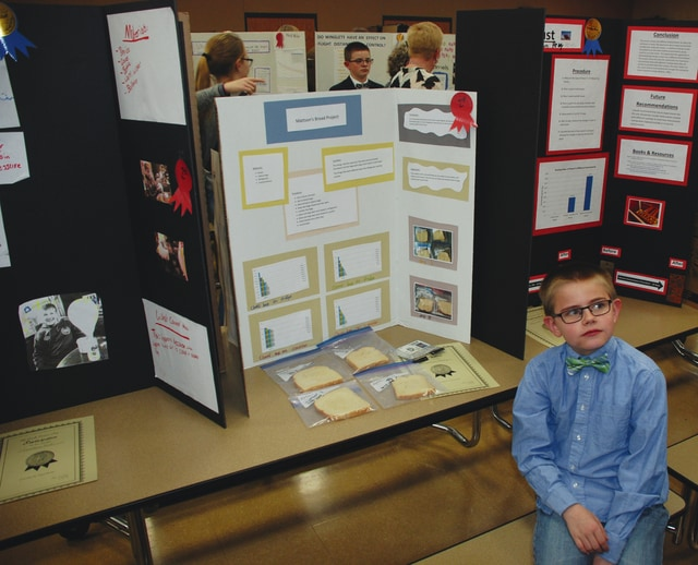 Pictured, Graham Elementary student Mattson Petry sits attentively and ready to explain his science fair project about bread. The school held its fifth-grade science fair Tuesday evening in the school cafeteria and the large room was brimming with projects, energy and visiting parents. A first round of judging was held prior to Tuesday with Graham High School students presiding and the top projects as judged by GHS students were presented to the public on Tuesday. See photo and names of winners from Tuesday's competition inside today's edition.