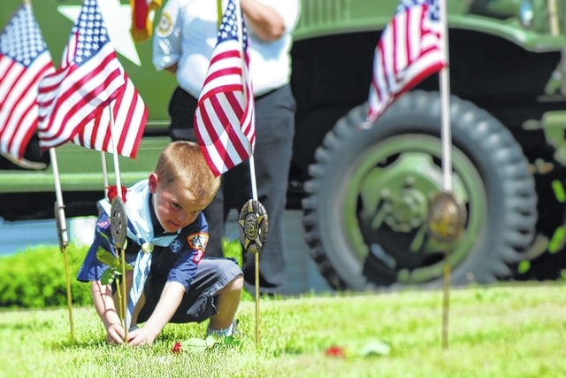 In North Lewisburg, Boy Scouts place flowers at a flag representing each conflict America has been involved in during Monday's ceremonies.