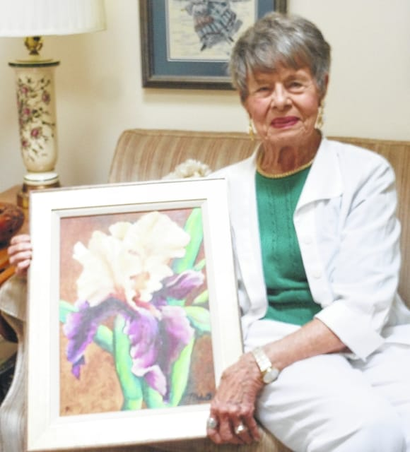 Margaret Manhart Denzer displays her painting, Iris, for the camera. To the left the viewer can see part of her needlepoint portrait of a classical skater.
