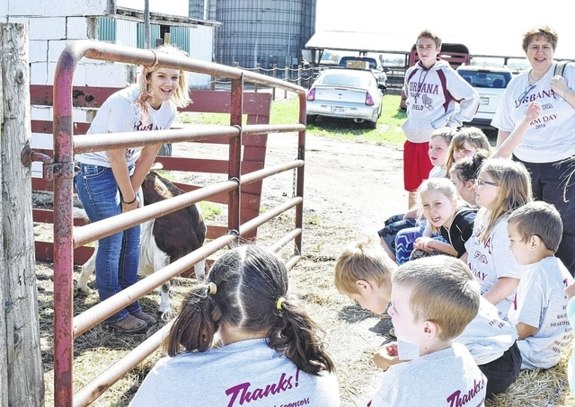 Urbana North Elementary students learn from FFA students and farmers about agriculture at the annual Urbana FFA Farm Day, held Friday at the Nelson Dairy Farm on South Dugan Road. Pictured is FFA student and Urbana High School freshman Aly Pierce teaching students about goats.