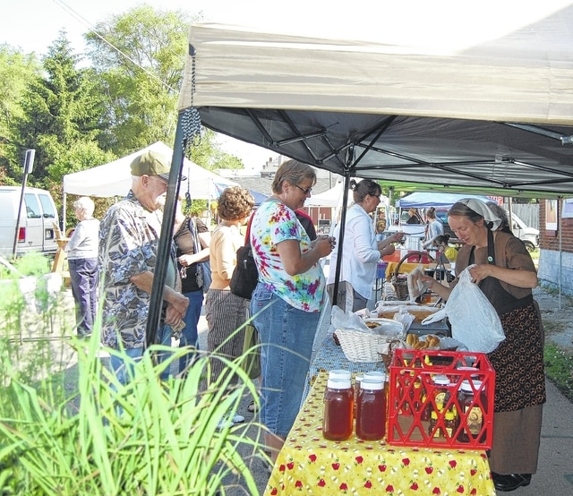 Customers and vendors take part in a previous Champaign County Farmers Market. Located off East Market Street in Urbana, the Farmers Market will open for the season at 9 a.m. Saturday.
