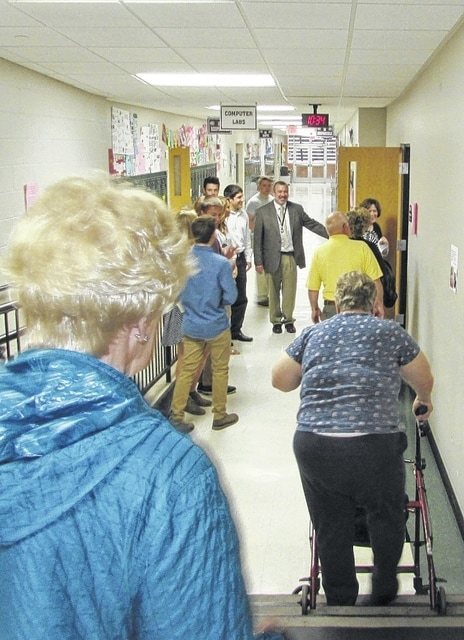 "Graham High School Principal Joe Hurst, center, gives a tour of the high school to attendees of a Wednesday morning ""Coffee and Conversation"" event. Staff and administrators discussed activities and programs in the school district and efforts to improve report cards and school offerings."