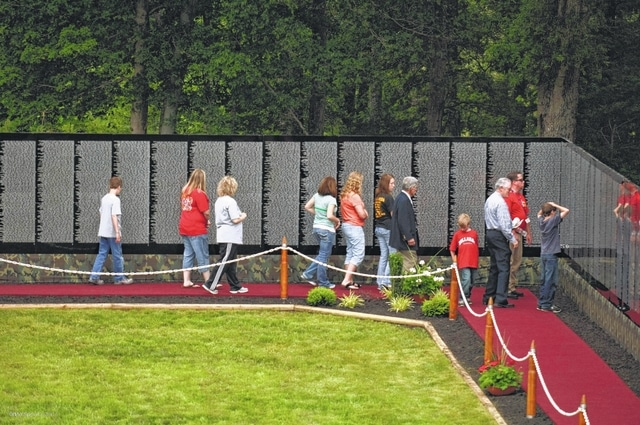 People view The Moving Wall exhibit during a stop in Camden, Tennessee. The half-size replica of the Vietnam Veterans Memorial in Washington, D.C., will be on display in Urbana June 9-13 at the former armory, 1412 N. Main St.