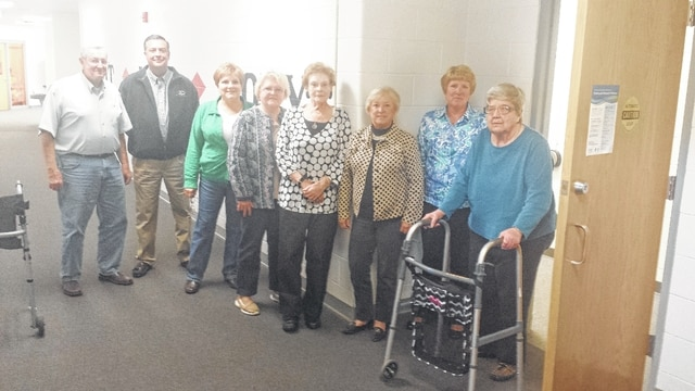Champaign County Memorial Foundation Board members Bill Miller, Dave Vernon, Annie Colliflower, Linda Erwin, Kris Sanders, and Vickie Henson observe as YMCA member Sally Mackey (with the walker) uses the automated door openers to enter the women's locker room.