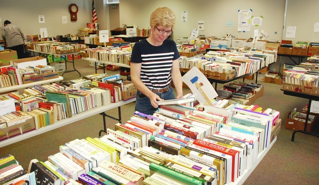 Alicia Schneider browses the expansive assortment of books available Friday at the Champaign County Library spring book sale. The sale continues at the Scioto St. location today from 9 a.m. to 3 p.m. Every spring and fall, the Friends of the Library holds a sale of discarded books from the library as well as book donations people bring in the week leading up to the book sale. Thousands of books are available covering all interests, ranging from hardback nonfiction, fiction, paperbacks, cookbooks, music CDs, DVDs, and much more. The Friends of the Library is a non-profit organization dedicated to raising funds to assist the Champaign County Library in purchasing children's books and supporting children's programs such as the summer reading program and baby, toddler and preschool story times. The Friends are actively seeking new members. For more info regarding joining the Friends of the Champaign County Library or regarding the book sale call 937-653-3811.