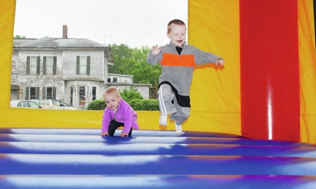 First Baptist Church in Urbana celebrated the opening of its new addition on Saturday. Games, refreshments and an open house were part of the activities. In photo, Kara Evans (left) and Rhys Evans enjoy the bounce house during the celebration. The church is located at 401 N. Main St.