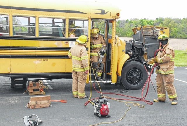 Agencies from around the area converged at the Johnson-St. Paris Fire District station on Saturday for an extrication class involving an auto and school bus. Pictured are first responders in training at the St. Paris site, which served as the host. The exercise lasted for much of Saturday and included a lunch break.
