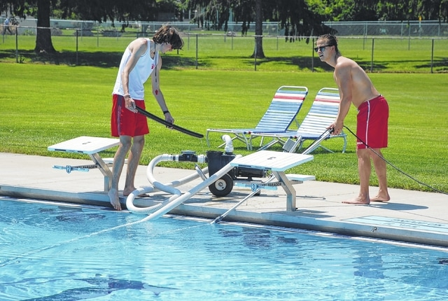 The city pool at Melvin Miller Park opened for the season on Monday. It is open Monday through Saturday from noon to 7 p.m. and on Sunday from 1-7 p.m. In photo, pool staffers Eli deNijs and Tristan Lynxwiler (in shirt) vacuum the pool while waiting on the season's first swimmers to arrive. Pool weather is predicted to arrive this week, just in time.