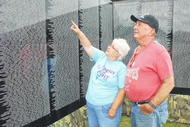Tom and Cheri Howard examine The Moving Wall, a traveling Vietnam War memorial, at the old armory on North U.S. Route 68 Friday afternoon. The wall is in Urbana through Monday, June 13, after arriving Thursday. Military Appreciation Day is being held today (Saturday) at Grimes Field in conjunction with the wall's visit to the armory.
