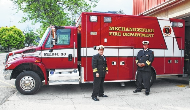 Mechanicsburg Assistant Fire Chief/EMS Chief Steve Castle, left, and Fire Chief Bob Keene, right, stand next to the village's new 2017 International Harvester squad. The $200,000-plus emergency vehicle was put into service on Friday.