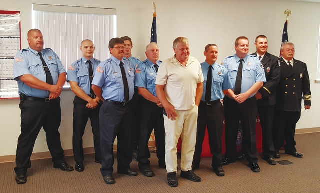 Multiple members of the JSP Joint Fire District who participated in a cardiac arrest call this year that saved Dan Owens stand with the patient on Tuesday during a ceremony to thank them for their lifesaving efforts.