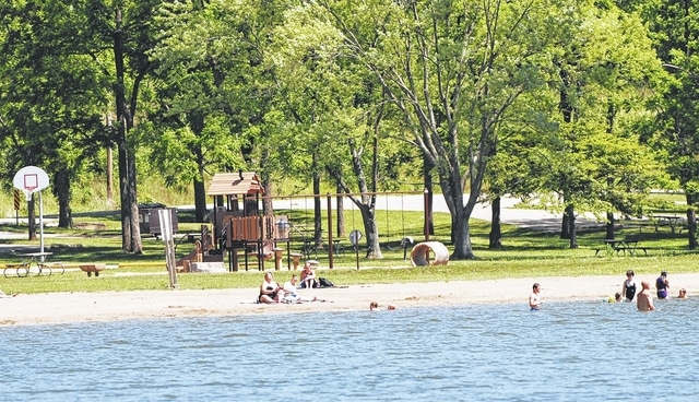 Sunbathers are pictured at Kiser Lake beach this week leading up to the long July 4 holiday weekend. Campers will converge on Kiser Lake this weekend for the holiday. Visitors to the beach will find new playground equipment (pictured in the background of this photo).