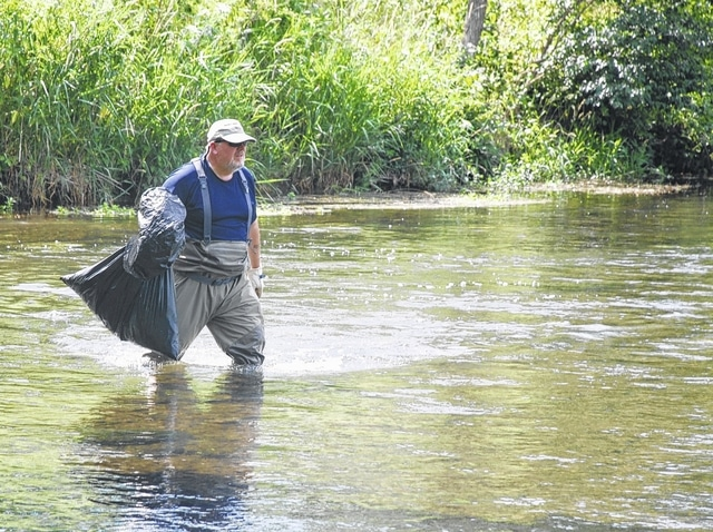 Mike May traveled all the way from Illinois on Saturday to help the Miami Valley Fly Fishers perform a periodic cleaning of the Mad River. May is pictured under the U.S. Route 36 bridge filling a trash bag with litter and other debris.