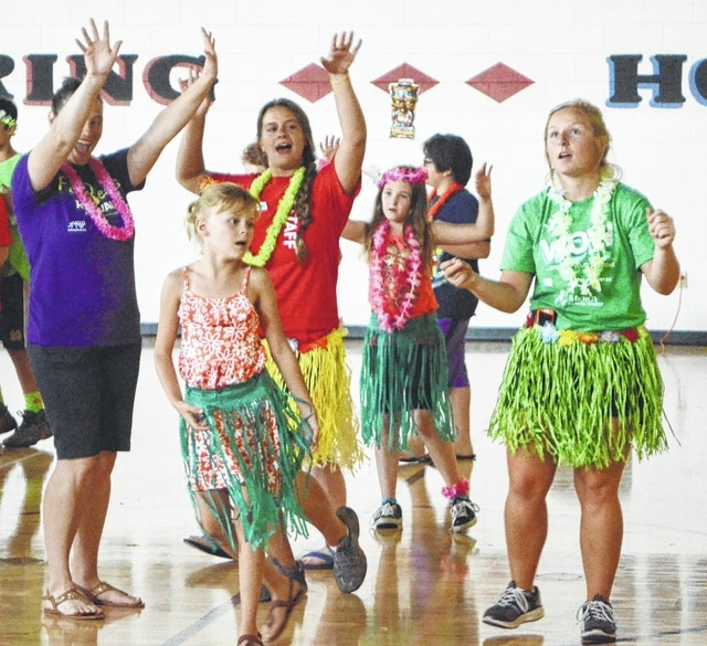 Champaign Family YMCA campers and chaperones dance during a luau at the Y on Thursday.