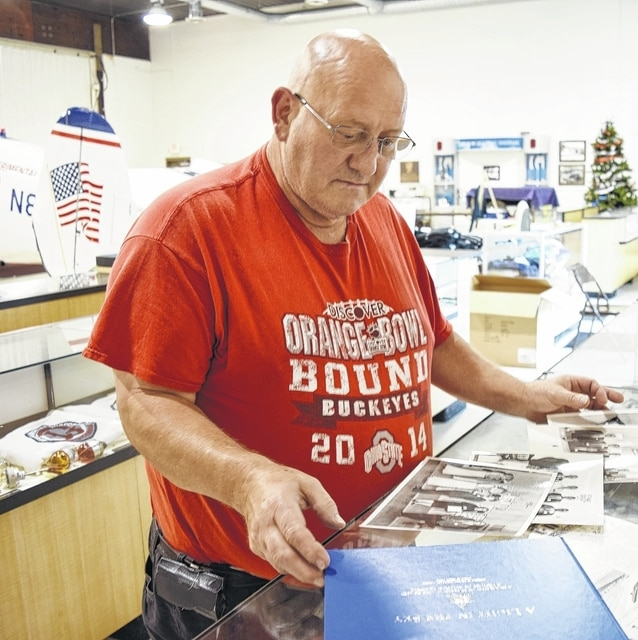 Grimes Quarter Century Club President Dean Minnich looks over historical documents related to Warren G. Grimes and Grimes Aerospace. The group will celebrate its 50th anniversary in September.