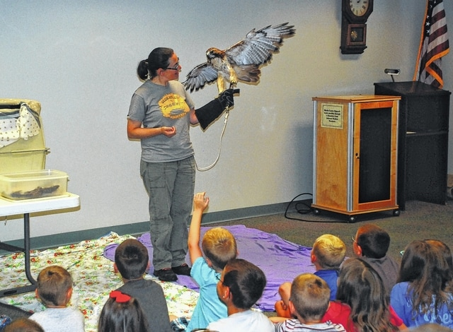 "During the ""Hunters of the Sky"" program held Wednesday at the Champaign County Library, Glen Helen Raptor Center Director Rebecca Jaramillo provided over 50 children with an up-close look at three raptors (birds of prey) – a hawk, a falcon and an owl. Jaramillo is pictured holding one of the center's 30 avian ambassadors – Will, a 3-year-old red-tailed hawk. The Glen Helen Raptor Center in Yellow Springs aims to improve the welfare of Ohio's raptors through educational programs and the rehabilitation of injured birds of prey."