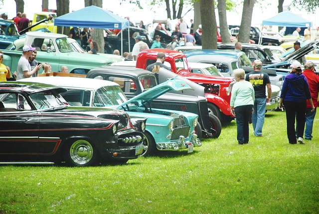 Admirers file through the lines of classic cars during the Champaign Cruisers Firecracker show on Monday in Urbana. A misty rain didn't dampen the activities around lunch hour.