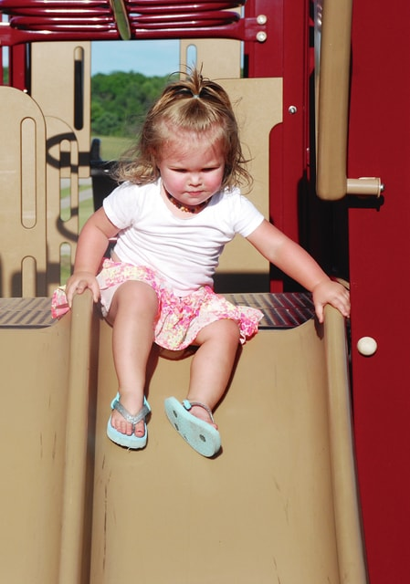 One-year-old Emily Noreikas carefully navigates her way down the slide at Melvin Miller Park. Noreikas was one of many children playing and biking around the park during a warm summer week.