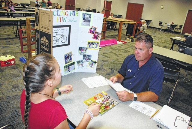 Junior fair judge Chris Logan, right, reviews Jorden Hillman's Champaign County Fair exhibit on bicycling during pre-fair judging sessions held last week at the Champaign County Community Center. The fair begins Aug. 5 and runs through Aug. 12.