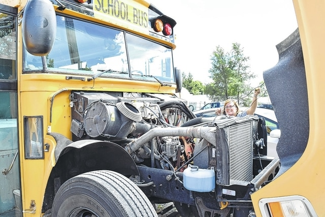 School has started for some districts in Champaign County, while others are preparing for the first day. Urbana City Schools bus driver Bonnie Fansler checks oil on her bus Monday. Fansler has been running her route already, as she drops off and picks up special needs students from Urbana for districts like Triad, Mechanicsburg and the Madison-Champaign Educational Service Center.