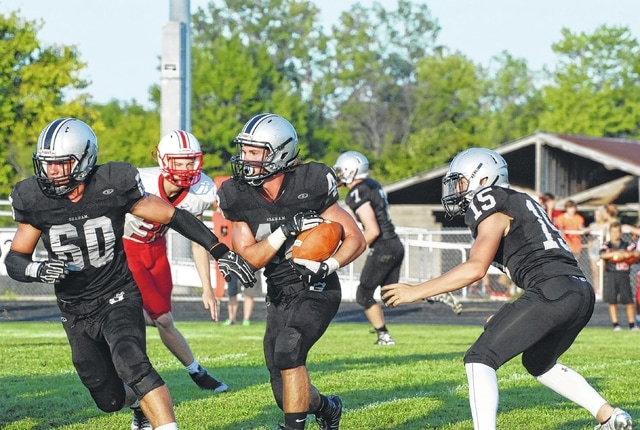 Graham's Lane Thompson carries the ball against Tippecanoe during last week's game. Also pictured are Falcons Forest Hyden (60) and Gage Braun (15).
