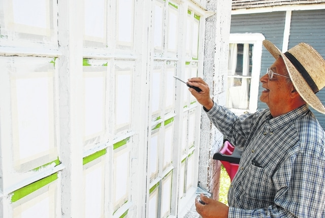 Professional painter Skip Jackson details the frames around each small window pane in the Westville Post Office's west window this week. The post office is getting a fresh paint job. Jackson said he has worked on other post offices in the area including one in Xenia and will work at the Urbana post office in the near future.