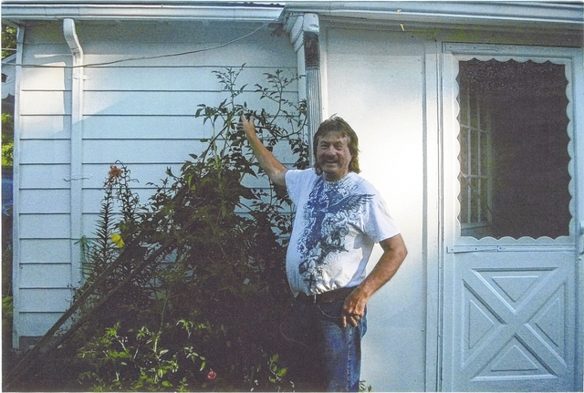 Stan Gilliam Sr. of 731 James Ave. stands proudly with his tomato plant on a recent summer day.
