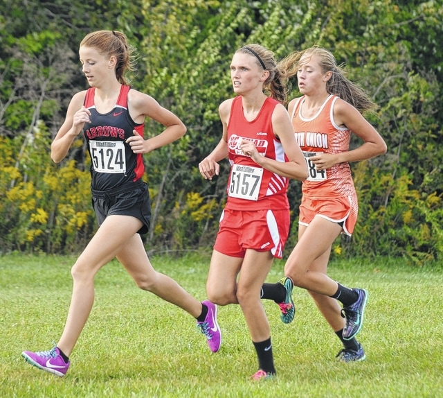 Triad's Holly Cole (5157) challenges for the lead early in Tuesday's high school girls run at Triad High School. Cole finished second in 20:55 to help the Cardinals finish second in the team standings.