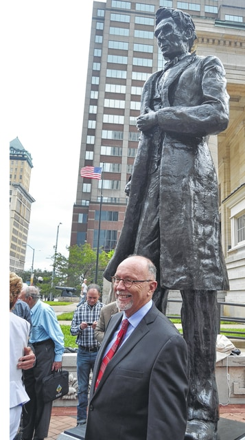Champaign County artist Mike Major stands in front of the Abraham Lincoln sculpture he was commissioned to create by the Lincoln Society of Dayton. The 11-foot-tall bronze statue, permanently on display next to the old courthouse in Courthouse Square at the corner of Third and Main streets in downtown Dayton, was unveiled during a ceremony held Sept. 17.