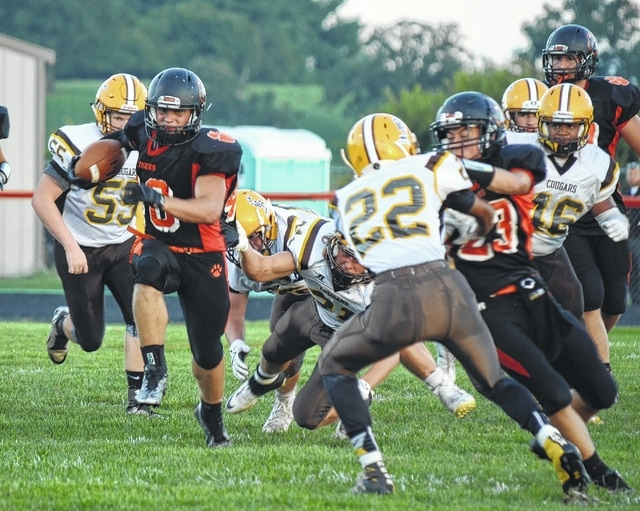 West Liberty-Salem's Brandon Wolfe (left) rips off a run up the middle against Kenton Ridge on Friday.