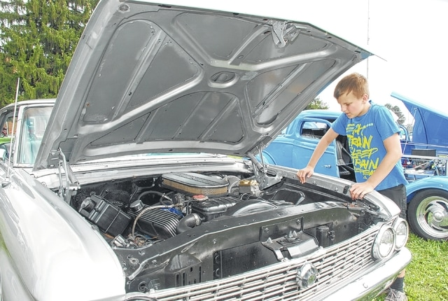 Alex Foulks, age 12 of St. Paris, admires one of the entries in the classic car show at Pony Wagon Days on Saturday. The annual festival expanded from one day in 2015 to three days in 2016.