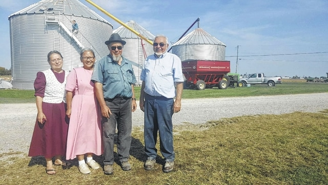 Enoch Eichorn smiles with his two sisters and a friend on his farm in Plumwood while volunteers help with his corn harvest. From left are: Lois Yoder, Esther Kauffman, Enoch Eichorn and Eli Hostetler.