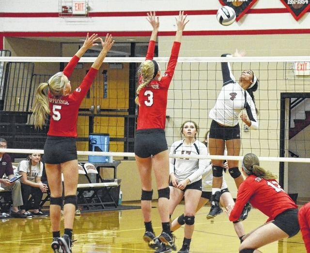 Urbana's Hunter Rogan smashes a ball past Tippecanoe defenders on Thursday in the Division II volleyball sectional at Tecumseh. Rogan, the CBC Player of the Year, led the Hillclimbers with 34 kills, 19 digs and 3 aces.