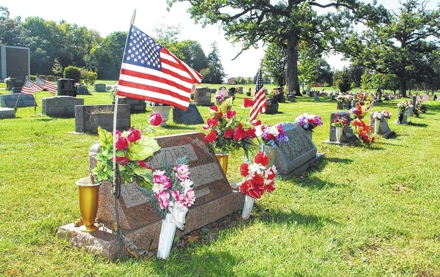 A U.S. flag flies Thursday beside a decorated gravesite at Oak Dale Cemetery in Urbana. The city is asking family members to limit decorations at each gravesite between Oct. 17 and Nov. 21 while groundskeepers complete the annual fall cemetery cleanup.
