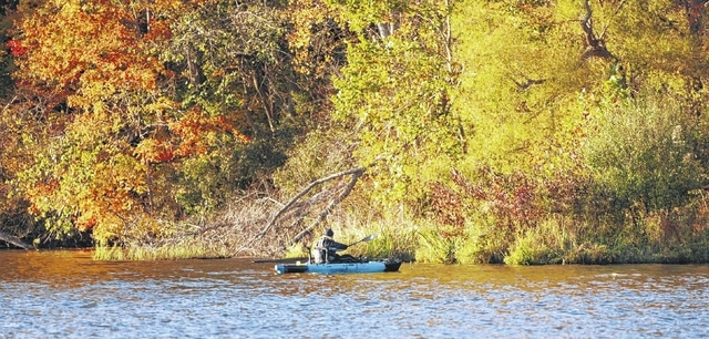 Luke Williams paddles toward the shore after fishing in Kiser Lake as the sun begins to set on Saturday. Williams was visiting the lake from nearby Wapakoneta. Yellow, orange and highlights of red characterize the foliage at Kiser Lake.