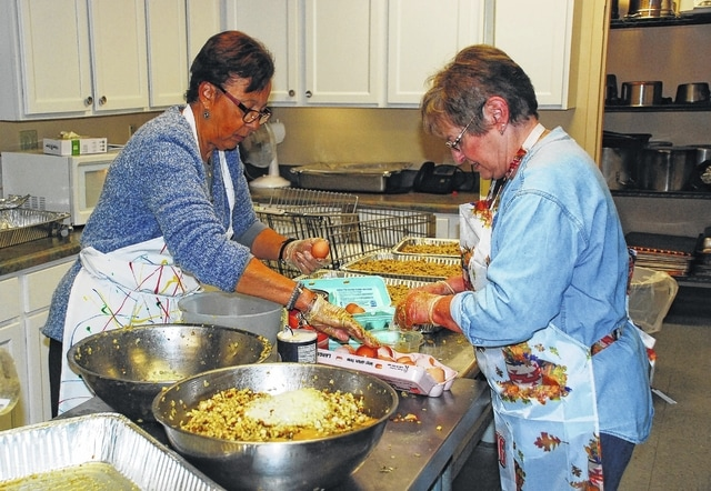 Local residents Michelle Porter, left, and Donna Flora, right, spent Wednesday afternoon volunteering their time to help prepare stuffing for the annual Thanksgiving Day meal that was served on Thursday at the Caring Kitchen in Urbana.