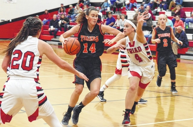 West Liberty-Salem's Mikalia McIntosh (14) splits the Triad defense on Tuesday at Triad, while Cardinals' post Audrey Lightle (4) tries to cut her off.