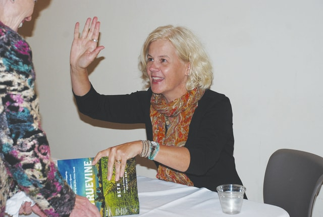 "Urbana native/author Beth Macy gives a high five to an old friend while signing a copy of her new book, ""Truevine,"" at the Urbana University Student Center on Tuesday."