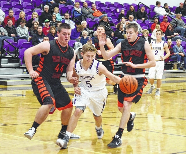 Mechanicsburg's Mack DeLong (5) dribbles between West Liberty-Salem's Nick Burden (left) and Tyler Louden (right) during Friday's OHC contest at Mechanicsburg High School. The Tigers used their size and athleticism to pester and frustrate the Indians all night.
